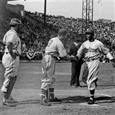 In this April 18, 1946, photo, Montreal Royals' Jackie Robinson, right, is congratulated by teammate George Shuba as he crosses home to score against the Jersey City Giants at Roosevelt Stadium in Jersey City, N.J.