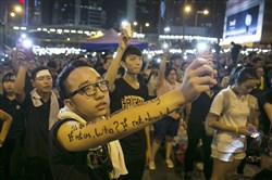 Student protester Kyle, 18, holds up his phone while chanting pro-democracy slogans during evening speeches at a rally Wednesday in Hong Kong. Thousands of pro-democracy activists continue to occupy the streets surrounding Hong Kong's financial district, calling for open elections and the resignation of Hong Kong's chief executive, Leung Chun-ying.