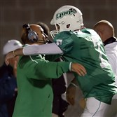 South Fayette quarterback Brett Brumbaugh hugs head coach Joe Rossi after breaking the WPIAL passing yardage in the second quarter against Steel Valley at South Fayette Stadium on October 3, 2014.