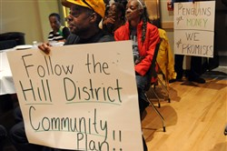 Hill District residents hold signs voicing opinions on the proposed development of the old Civic Arena Site during an October meeting.