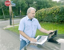 Matt Graham, a landscape architect who has designed a precision mapping system for water runoff, checks his program Wednesday at the intersection of Chislett and Vetter streets.