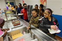 Twelve-year-old Aacia Sayyed, far right, leads a line of students getting food in the Wilkinsburg Junior/Senior High School's after school meal program. The school offers a third meal for students every day until 5 p.m.