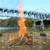About 30 volunteers cleaned up a sandbar on the Monongahela River that the Hays bald eagles have used to stage their hunting and teach their young how to hunt and fish. Volunteers watch as a pile of wood from Monongahela River near Sandcastle was burned on Saturday.