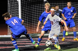 Upper St. Clair's Shayne Sibley (in light uniform) sets up a goal against Chartiers Valley during a match last month.