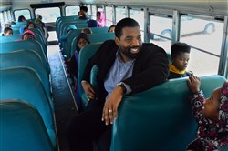Pittsburgh Faison K-5 principal Russell Patterson rides on the school bus with students from East Hills to the school in Homewood on Friday.