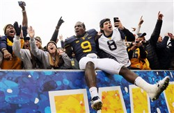 West Virginia's K.J. Dillon celebrates with the fans after defeating Baylor at Milan Puskar Stadium in Morgantown on Saturday afternoon.