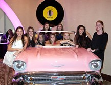 Oakland Catholic High School students pose with a classic pink car at the Leading Ladies Gala XI.