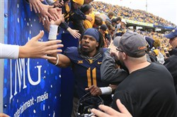 West Virginia senior Kevin White, shown celebrating with fans after a 41-27 win Oct. 18 against Baylor in Morgantown, W.Va., is looking forward to a bowl game.