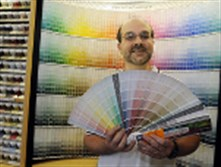 Larry Demas, a worker at the Westmoreland Supply Paint & Decorating Center in Ross, displays paint colors in this 2009 photo.