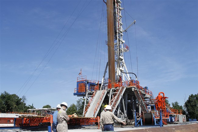 In this 2011 photo, Range Resources workers stand near the rig that drills into the shale at a well site in Washington, Pa. Pennsylvania's counties and municipal governments will see another drop in the annual fee revenue they get from Marcellus Shale gas wells.
