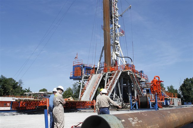 Range Resources workers stand near the rig that drills into the shale at a well site in Washington, Pa.