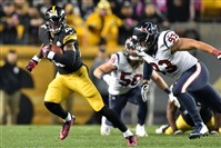 Steelers running back Le'Veon Bell carries as he's defended by Texans defensive end Jared Crick in the first quarter at Heinz Field.
