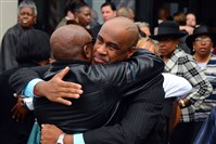 Dante Alston, a longtime friend of Omar Hodges, comforts another mourner after Mr. Hodges' funeral at Covenant Church of Pittsburgh in Wilkinsburg.
