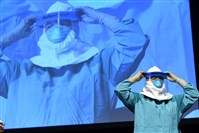 Barbara Smith, a registered nurse with Mount Sinai Health Systems, demonstrates the proper technique for donning protective gear during an Ebola educational session for health care workers in New York City.