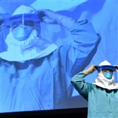 Barbara Smith, a registered nurse with Mount Sinai Health Systems, demonstrates the proper technique for donning protective gear during an Ebola educational session for health care workers Tuesday at the Jacob Javits Center in New York City.