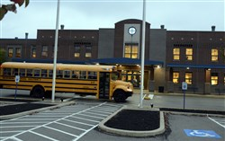 A school bus passes in front of the Norwin High School entrance.