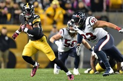 Steelers running back Le'Veon Bell carries as he is defended by Texans lineman Jared Crick in the first quarter at Heinz Field Monday night.