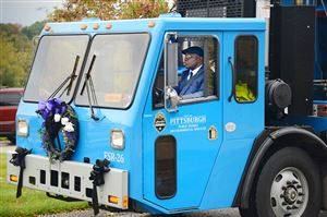 William Lesesne Jr., 56, of Hazelwood, co-worker of city sanitation worker Omar Hodges, drives a garbage truck to Mr. Hodge's funeral at Covenant Church of Pittsburgh in Wilkinsburg.