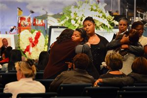 Family and friends comfort each other at the funeral of city sanitation worker Omar Hodges at Covenant Church of Pittsburgh in Wilkinsburg.