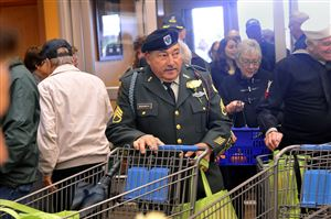 David Marchetti, center, a retired Army Ranger with 26 years in the service, wheels his cart into the new Commissary for military families and veterans after the ribbon was cut in Moon.