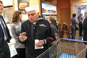 Bob Massimini, a Navy veteran from Hopewell, samples a free cupcake as he arrives at the new Commissary for military families and veterans in Moon.