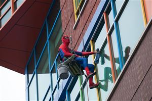 Rick Bollinger, dressed as Spider-Man, cleans a window at Children's Hospital of Pittsburgh of UPMC in Lawrenceville.