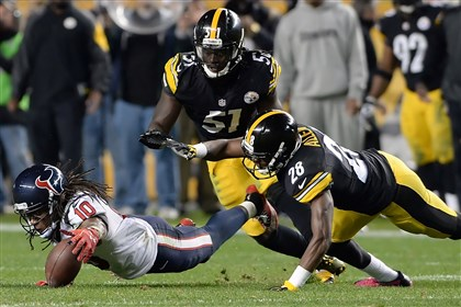 The Texans' DeAndre Hopkins fumbles in front of the Steelers' Cortez Allen and Sean Spence in the fourth quarter Monday night at Heinz Field. Troy Polamalu recovered the fumble.