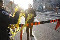 Police officers gather police tape following shootings in downtown Ottawa.