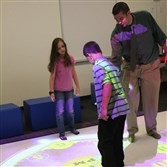 Twin Rivers teacher Ed Camic guides students Aliyah Burger and Devin Long in the SMALLab.