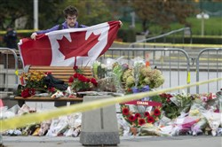 A man spreads out a Canadian Flag near the National War Memorial near Parliament Hill in Ottawa on Thursday, Oct. 23, 2014. Canadians are mourning the loss of Cpl. Nathan Cirillo, the army reservist who was shot dead as he stood guard before the Tomb of the Unknown soldier on Wednesday.