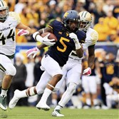 West Virginia's Mario Alford runs past Baylor defenders for a receiving touchdown late in the fourth quarter of last weekend's game in Morgantown, W.Va., Saturday, Oct. 18, 2014. West Virginia won 41-27.