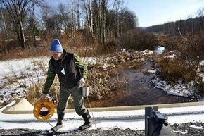 Department of Environmental Protection inspector John Sengle prepares to take water samples from Hawk Run near Philipsburg last January. The DEP is proposing a new policy to standardize the way it handles oil and gas well site inspections, enforcement actions and complaints that drilling has damaged water supplies.