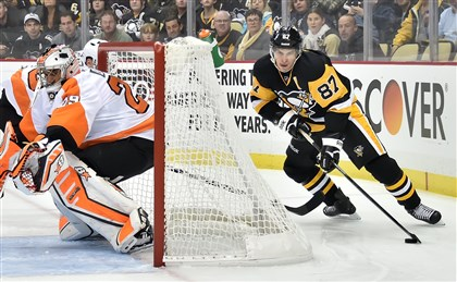 Sidney Crosby controls the puck behind Flyers goaltender Ray Emery in the first period Wednesday at Consol Energy Center.