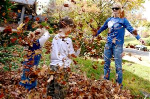 Erica Cillo of Squirrel Hill throws a pile of leaves onto her son, Trip Cillo, 4, in white, and her nephew, Lain Brown, 2, while raking at her home on Beechwood Boulevard.