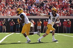 West Virginia quarterback Clint Trickett hands off to running back Wendell Smallwood in the Mountaineers' Big 12 win at Oklahoma State Saturday.