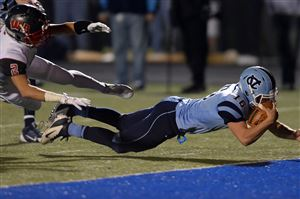 Central Valley quarterback John George dives into the end zone for a touchdown against West Allegheny's Tyler Scanlon in the first half at Central Valley High School in Monaca.