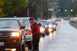 Marysville School District security checks cars lined up Saturday along 108th Street NE arriving at Marysville Pilchuck High School to pick up students' belongings Marysville, Wash. Parents and guardians received phone calls and emails saying that they could retrieve belonging Saturday morning that were left at the school when students were evacuated Friday.