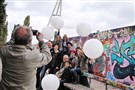 At the Mauerpark, on the site of the former Berlin Wall, a group celebrates with balloons. Illuminated balloons like these will line a section of the former Wall for the 25th anniversary of its fall next Sunday.