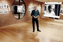 "Brian Cohen stands near his work, to the left, and near images of ""Bill Strickland "" by Scott Goldsmith, to the right, at the Manchester Guild studio."