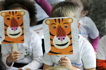 "Youngsters hold tiger masks during a reading of ""Mr. Tiger Goes Wild"" by Peter Brown at the Hyundai Club West Lounge of Heinz Field. The event was an attempt to set a record for the world's largest vocabulary lesson."