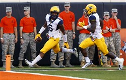 West Virginia safety Dravon Henry (6) runs in an interception for a touchdown against Oklahoma State during the fourth quarter at Boone Pickens Stadium. West Virginia won 34-10.