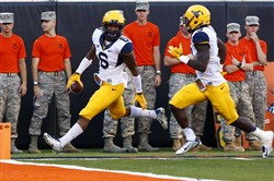 West Virginia safety Dravon Henry (6) runs in an interception for a touchdown against Oklahoma State during a game last year at Boone Pickens Stadium. West Virginia won 34-10.