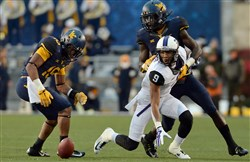 West Virginia's Terrell Chestnut reaches to recover a fumble by TCU's Josh Doctson in the third quarter Saturday at Milan Puskar Stadium in Morgantown, W.Va. Chestnut returned the fumble for a touchdown.
