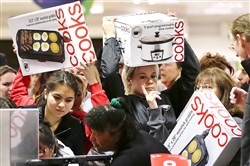 Shoppers rush to grab electric griddles and slow cookers on sale for $8 shortly after the doors opened at a Las Vegas J.C. Penney store in November 2012.