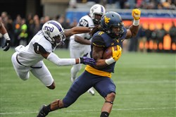 West Virginia's Kevin White jukes past TCU defender Chris Hackett (1) during the first quarter of a game last week in Morgantown, W.Va.
