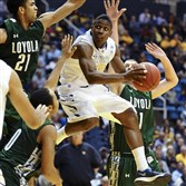 West Virginia's Juwan Staten drives by Loyola Maryland defenders during the second half of an game last year in Morgantown. West Virginia won 96-47.