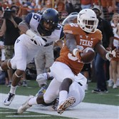 Texas' Johnathan Gray is pursued by West Virginia's Terrell Chestnut as he reaches for the goal line to score a touchdown in the first half Saturday in Austin, Texas.