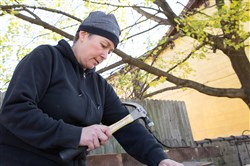 "Artist Dee Briggs helps the ""Gold Team"" remove nails from salvaged wood in an effort to perform a soft demolition on the House of Gold. She hopes to someday build a coffee shop where the House of Gold used to be, using repurposed materials."