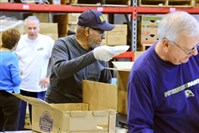 Richard Montgomery, 69, of East Liberty and other volunteers pack food at the Greater Pittsburgh Community Food Bank in Duquesne on Nov. 11.