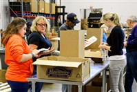 Grace Woolard, 15, her mom, Kathleen, 51, of Lincoln Place, Richard Montgomery, 69, of East Liberty and other volunteers pack food at Greater Pittsburgh Community Food Bank in Duquesne on Nov. 11.